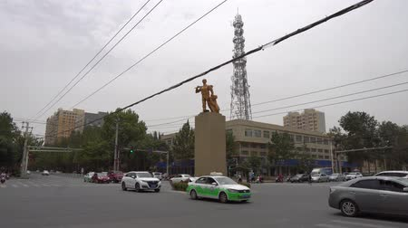 yosma : Hotan Busy Ring Road with Centered Brazen Statue of a Uyghur Peasant with a Hat Holding a Shovel and Clothes Stok Video