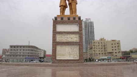 elnök : Hotan Tuanjie Square Brazen Statue of Chairman Mao Zedong Shaking his Hand with Uyghur Elder on a Rainy Day Stock mozgókép