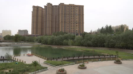 yosma : Hotan Yuquan River Lake Park High Angle View with Residential Buildings at Cloudy Day