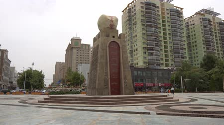 vytesaný : Hotan Tuanjie Square Statue of a Huge Stone with Chinese and Uyghur Inscriptions with Residential Buildings at Background