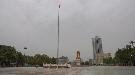 elnök : Hotan Tuanjie Square High Waving Chinese Flag with People and Brazen Chairman Mao Zedong Statue at Background