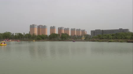gongyuan : Hotan Picturesque Kunlunhu Lake Park with Sailing Boats and a Row of Residential Buildings at Background Stock Footage