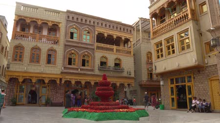 temyiz : Hotan Renovated Old City Square with Walking Chinese Tourists and a Statue made out of Red Colored Flowers Stok Video