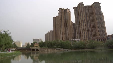yosma : Hotan Yuquan River Lake Park View of Relaxing Walking People at Residential Buildings at Sunset on a Cloudy Day