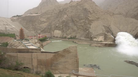 yosma : Hotan Wuluwati Hydroelectric Power Generation Dam High Angle View of the Released River Stream and Pagoda on a Foggy Day Stok Video