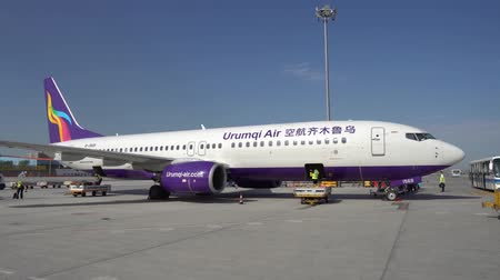 província : Busy Airport Ground Staff Workers are loading and preparing for the next flight on a Urumqi Air Aircraft on a Picturesque Sunny Day