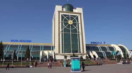 アピール : Nur-Sultan Astana City Main Railway Station. Front View with Kazakh Flags on a Sunny Blue Sky Day