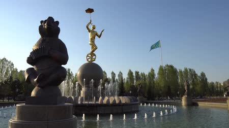 brazen : Nur-Sultan Astana Capital Circus Fountain with Bear and Brazen Statue of Man Holding a Umbrella while Moving with a Unicycle