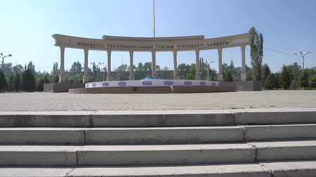 silk road : Taraz Presidential Park with Pillars Gate and Huge Waving Kazakhstan Flag on a Sunny Blue Sky Day Stock Footage