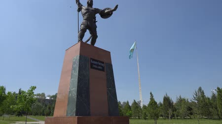 dárda : Taraz Presidential Park Statue of Koshek Batyr Holding a Spear with Huge Waving Kazakhstan Flag at Sunset on a Blue Sky Blue Sky Day