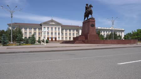 merkezi : Taraz Akimat City Hall on background with statue of Baydibek Batyr Riding a Horse on a Blue Sky Day Stok Video