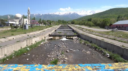 silk road : Esik Issyk River Streaming from the Snow Capped Mountains at the Central Mosque View on a Sunny Blue Sky Day Stock Footage