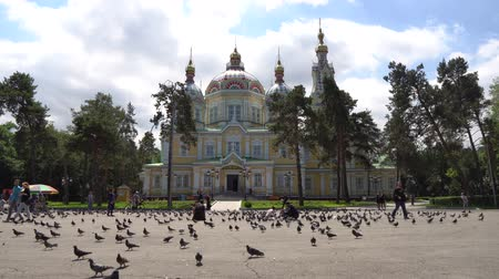 felemelkedés : Almaty Russian Orthodox Christian Zenkov Ascension Cathedral Low Angle Frontal View in Panfilov Park with Pigeons and People on a Sunny Blue Sky Day