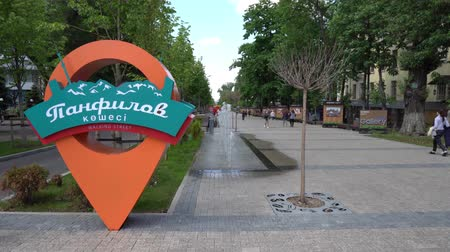 штифт : Almaty Panfilov Walking Street with Pointing Road Sign and Young People Cloudy Blue Sky Day