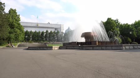 ügyintézés : Almaty Presidential Residence Fountain and a Girl Sitting on a Cloudy Blue Sky Day Stock mozgókép