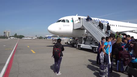 silk road : At Almaty International Airport Passengers are Waiting Outside for Boarding the Air Astana Aircraft Plane