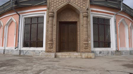 artifacts : Qurghonteppa Bokhtar Teppa Modern History Museum Monument Main Gate Entrance Front View with Waving Tajikistan Flag on a Cloudy Rainy Day