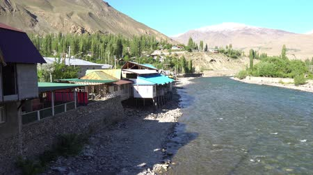 アピール : Khorugh Gunt River Streaming the Snow Capped Mountains and Panj at the Residential Houses on a Sunny Blue Sky Day