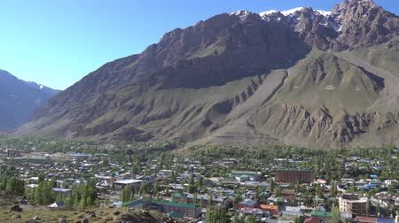 surroundings : Khorugh Cityscape and Landscape with Snow Capped Mountains on the Afghanistan Side on a Sunny Blue Sky Day Stock Footage