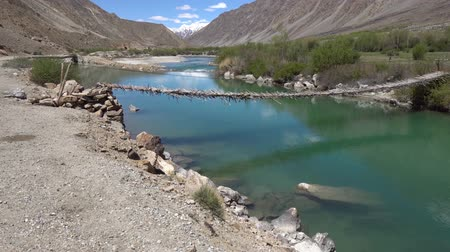 gorno : Pamir Highway Wooden Plank Bridge for Pedestrians Hanging over the Gunther River with Snow Capped Mountains at Sunset on a Blue Sky Day Stock Footage