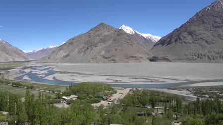 Pamir Highway Wakhan Corridor Landscape View from Abrashim Qala Fortress in Zong of the Snow Capped Mountains of Afghanistan on a Sunny Blue Sky Day Stockvideo