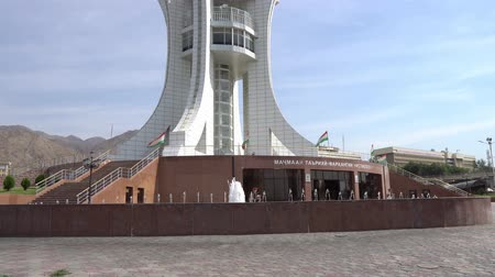 silk road : Khujand Stella Ring Road Side View with Fountains and Waving Tajikistan Flags on a Sunny Blue Sky Day