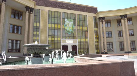 heykel : Khujand Cultural Palace Sugdiyon Frontal View with Fountain and Waving Tajikistan Flag on a Sunny Blue Sky Day