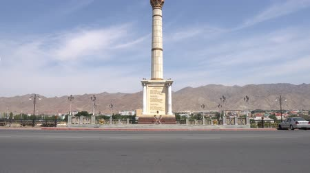 silk road : Khujand Stella with Patriotic Inscriptions and Tajikistan Coat of arms on a sunny blue sky day Stock Footage