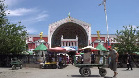 silk road : Khujand Panjshanbe Main Bazaar Front View with Busy People and a Man Moving his Carriage on a Sunny Blue Sky Day Stock Footage