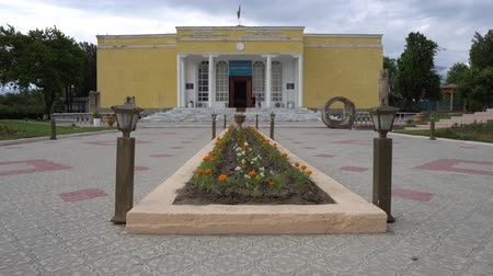 syrdarya : Penjikent Rudaki Historical Museum Frontal View with Waving Tajikistan Flag on a Cloudy Blue Sky Day