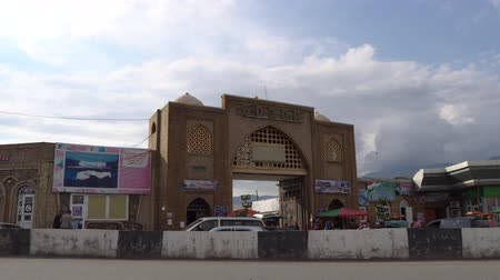 アピール : Penjikent Bazaar Entrance Gates Side View with Driving Cars and Walking People at Sunset on a Cloudy Blue Sky Day 動画素材