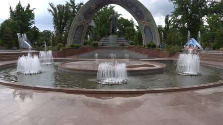monção : Dushanbe Abu Abdullah Rudaki Park Statue Frontal View with Fountains and People on a Cloudy Rainy Day