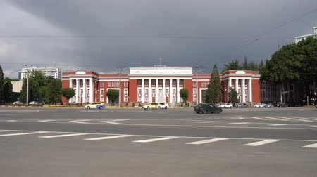 silk road : Dushanbe Parliament of the Republic of Tajikistan. Frontal view with busy traffic on a cloudy rainy day Stock Footage