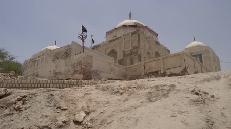 hacı : Sukkur Adam Shah Ji Takri Tomb on a Low Angle Back View with Islamic Waving Flags on a Sunny Blue Sky Day