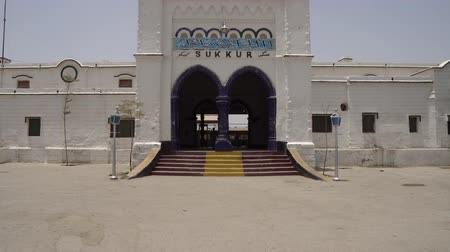 Sukkur Main Railway Station Frontal Entrance View with Waving Pakistan Flag on Roof and a Man Coming out on a Sunny Blue Sky Day 動画素材