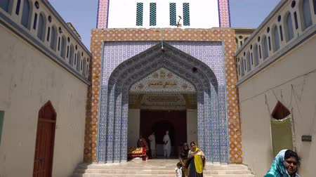 hacı : Sehwan Sharif Hazrat Laki Shah Sadar Shrine Entrance into the Main Tomb with Pilgrim on a Sunny Blue Sky Day