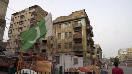 Karachi Waving Pakistan Flag at a Street in a Residential Area with Busy Traffic and People Walking on a Cloudy Day