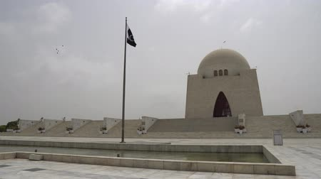 muhammad ali : Karachi Mazar-e-Quaid Jinnah Mausoleum Frontal View with Pond and Waving Pakistan Flag on a Cloudy Day
