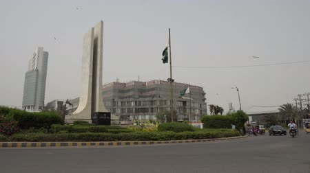 Karachi Do Talwar Two Sword Monument Ring Road at Khayaban e Iqbal Road with Waving Pakistan Flag and Busy Traffic on a Cloudy Day