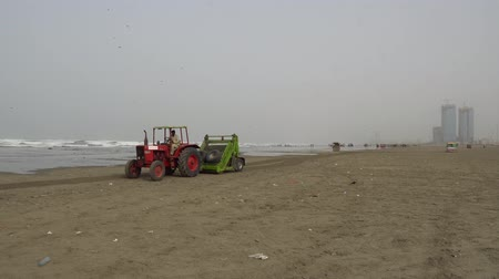 Karachi Clifton Beach Tractor Cleaning the Dirty Shore and Garbage at Morning on a Cloudy Day
