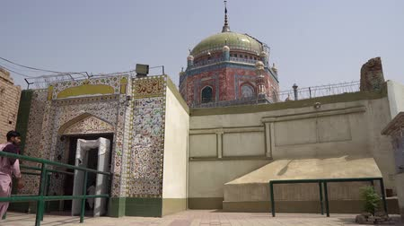 hilâl : Multan Hazrat Shah Shams Sabzwari Shrine Muslim Man at Shalwar Kameez is Entering the Mausoleum on a Sunny Blue Sky Day Stok Video