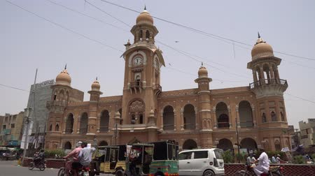 штаб квартира : Multan Ghanta Ghar Clock Tower City Government Headquarters Side View with Busy Road Traffic on a Blue Sky Sunny Day
