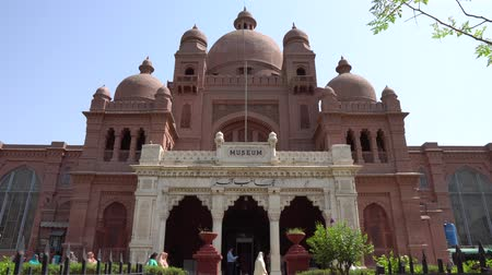 exiting : Lahore Museum Wonder House Entrance Frontal View with Visitors Entering and Exiting the Building on a Sunny Blue Sky Day