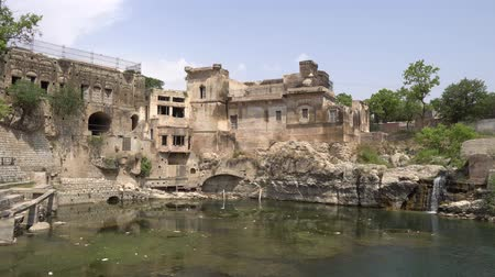 shiva : Chakwal Qila Katas Raj Hindu Temples Dedicated to Shiva Surround a Pond with a Waterfall on a Sunny Blue Sky Day Stock Footage