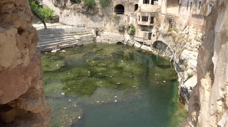Chakwal Qila Katas Raj Hindu Temples Dedicated to Shiva Surround a Pond with a Waterfall on a Sunny Blue Sky Day Stock Footage
