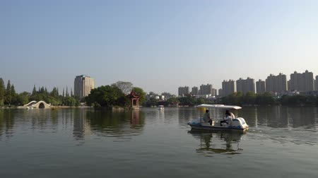 gongyuan : Wuhu Anhui Dajing Lake at Jinghu Gongyuan Park with Tourists and Visitors Sailing with Boats During Sunset