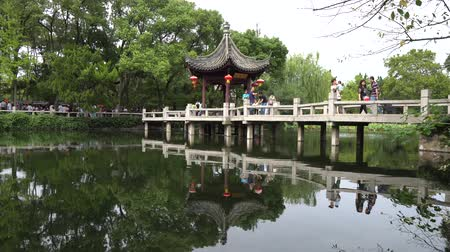 павильон : Shanghai Nanxiang Old Town Canal City Picturesque Guyi Gongyuan Chinese Garden at Pavilion and Stone Bridge at Lake and Walking People