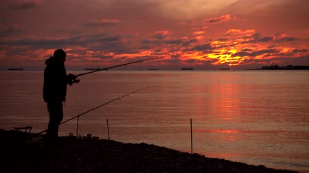 fisher : Fisherman and majestic sunset over water. 4k quality video. Stock Footage