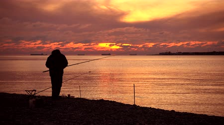 fisher : Fisherman catch fish, majestic sunset over water. 4k quality video.