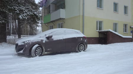 Snowfall in the city, snow covered car neer house.